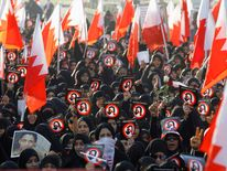 Protesters hold banners and Bahraini flags