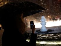 A woman takes a photo of a snow man that was erected at the fountain at Lincoln Center during New York Fashion Week in New York