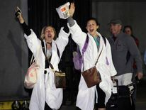 Passengers cheer after disembarking from the Carnival Triumph cruise ship after reaching the port of Mobile, Alabama,