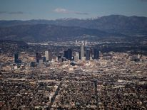The Los Angeles skyline and the San Gabriel Mountains are seen in this aerial photo