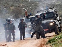 An Israeli border policeman fires tear gas at Palestinian stone throwers in the West Bank village of Kusra, near Nablus