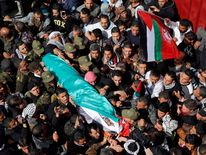 Palestinians carry the body of Arafat Jaradat as it arrives at his home before his funeral in the West Bank village of Sa'ir near Hebron