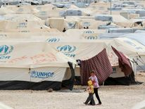 Syrian refugee children walk along tents at the Al Zaatri refugee camp in the Jordanian city of Mafraq