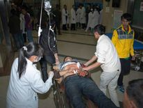 An injured man is pushed on a gurney at a hospital after a knife attack at Kunming railway station, Yunnan province