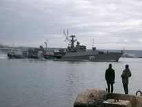 People watch a Russian Navy ship enter the Crimean port city of Sevastopol