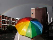 A woman carries an rainbow-coloured umbrella as she walks past a rainbow appearing over a housing estate in east London
