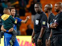 Brazil's Neymar carries a young soccer fan at the end of their international friendly soccer match against South Africa at the First National Bank (FNB) Stadium, also known as Soccer City