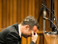 Olympic and Paralympic track star Oscar Pistorius reacts while a witness testifies during the fourth day of his trial for the murder of his girlfriend Reeva Steenkamp at the North Gauteng High Court in Pretoria