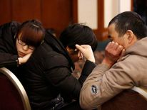 Family members of a passenger onboard the missing Malaysia Airlines flight MH370 react as they listen to a briefing from the airline company at a hotel in Beijing