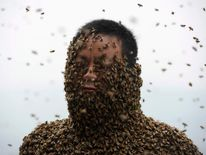 She Ping, a 34-year-old beekeeper, is seen during an attempt to cover his body with bees, in Chongqing municipality.