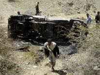 People inspect the wreckage of a car hit by an air strike in the central Yemeni province of al-Bayda