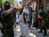 A pro-Russian armed man escorts Ukrainian journalist Irma Krat after a news conference in Slaviansk