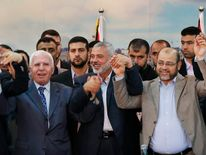 Senior Fatah official Azzam Al-Ahmed, head of the Hamas government Ismail Haniyeh and senior Hamas leader Moussa Abu Marzouq hold hands after announcing a reconciliation agreement in Gaza City