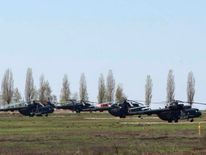 Russian military helicopters are seen in a field outside the village of Severny in Belgorod region near the Russian-Ukrainian border.