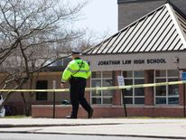 Police guard the front of Jonathan Law High School in Milford