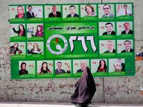 A woman walks past a PUK campaign poster for Iraq's parliamentary elections in Sulaimaniya