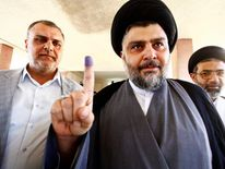 Shiite cleric Moqtada al-Sadr shows his ink-stained finger at a polling station during parliamentary election in Najaf