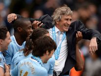 Manchester City's manager Manuel Pellegrini is thrown into the air by his team as they celebrate winning the English Premier League trophy following their soccer match against West Ham United