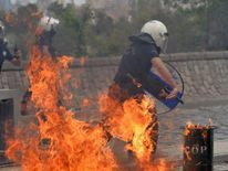 Riot police run away from the flames of a fire bomb thrown by protesters as they demonstrate to blame the ruling AK Party (AKP) government on mining disaster in western Turkey, in Ankara
