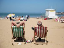 A couple sit on the beach in deckchairs in Margate