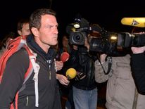 Journalists surround convicted rogue trader Jerome Kerviel as he arrives on the Franco-Italian border in Menton