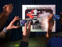 "Journalists take photographs of a display referring to ""BlackShades"" malware during a news conference by the U.S. Attorney for the Southern District of New York to announce law enforcement action to target creators and purveyors of malicious computer soft"