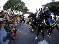 Police use tear gas to impede native Brazilians from marching towards the Mane Garrincha soccer stadium during a demonstration in Brasilia