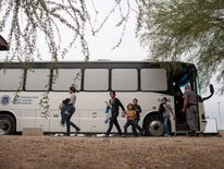 Migrants, consisting of mostly women and children, disembark from a U.S. ICE bus at a Greyhound bus station in Phoenix