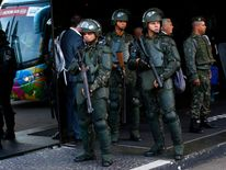 Brazilian army personal stand guard as the England team arrives at their team hotel in Rio de Janeiro