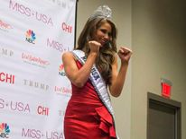 Miss Nevada Nia Sanchez poses in a taekwondo martial art stance for the media at a news conference after she won the 2014 Miss USA beauty pageant in Baton Rouge, Louisiana