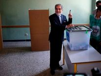 Afghan presidential candidate Abdullah Abdullah  poses as he casts his vote at a polling station in Kabul.