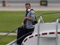 England's Rooney arrives back from the 2014 World Cup in Brazil at Manchester airport