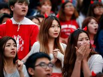 South Korean soccer fans react as they watch a live television broadcast of their 2014 World Cup Group H soccer match against Belgium, in Seoul