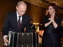 Vladimir Putin plays an accordion as Cristina Fernandez watches at a dinner in Argentina