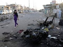 A girl walks past site of bomb attack at market in Baghdad's Sadr City
