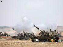 An Israeli mobile artillery unit fires towards Gaza