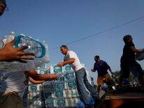 Volunteers unload drinking water from a truck outside Waite High School in Toledo,