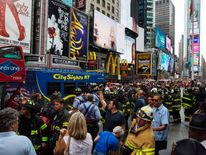 Emergency personnel gather to assess injuries and damage following a collision between two tour buses in the Times Square region of New York