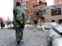 An armed pro-Russian separatist stands in front of damaged buildings following what locals say was shelling by Ukrainian forces in Donetsk