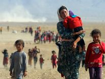 Displaced people from the minority Yazidi sect, fleeing violence from forces loyal to the Islamic State in Sinjar town, walk towards the Syrian border.