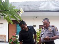 Police examine the suitcase in which the body of an American woman was found, at a police station in Nusa Dua