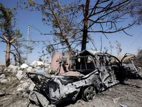 The wreckage of a car belonging to Islamic State militants lies beside a tree after it was targeted by a U.S. air strike at Mosul Dam