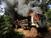 A logging truck burns after it was discovered and set on fire by Ka'apor Indian warriors in the Alto Turiacu Indian territory