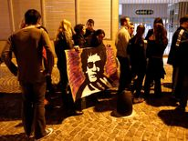 Fan displays a drawing of Argentine musician Gustavo Cerati, as people line up to attend his funeral in Buenos Aires