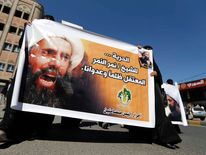 Shi'ite protesters carry a poster of Sheikh Nimr al-Nimr during a demonstration outside the Saudi embassy in Sanaa