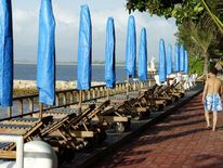 CHINESE TOURIST WALKS PAST EMPTY CHAIRS ON SANUR BEACH.