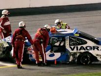 Rescue workers rush to Mark Martin's car, which advertised Viagra, after crash in Pepsi 400 at Daytona