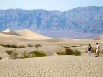Tourists walk in dunes in Death Valley National Park, California
