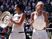 Marion Bartoli of France holds her trophy, the Venus Rosewater Dish, after defeating Sabine Lisicki of Germany in their women's singles final tennis match at the Wimbledon Tennis Championships, in London