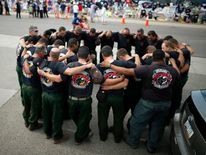 Firefighters pray in front of a memorial dedicated to the 19 firefighters killed in the nearby wildfire in Prescott